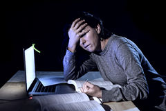 Young desperate university student girl in stress for exam studying with books and computer laptop late at night Royalty Free Stock Image