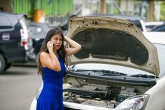 Upset Asian Japanese woman in stress stranded on street suffering car engine failure having mechanic problem calling on mobile royalty free stock image