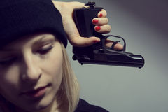 Young desperate woman with a gun in his hand Stock Image