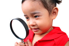 Young detective. Young girl looking true the magnify glass Royalty Free Stock Photo