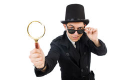 Young detective in black coat holding magnifying. Glass isolated on white Stock Photo