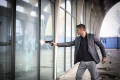 Young detective or policeman or mobster firing a. Well dressed handsome young detective or policeman or mobster standing in an urban environment aiming and royalty free stock image