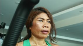 Young determined and athletic Asian Indonesian sport woman training fitness working hard at gym doing elliptical machine workout. Close up face shot of young stock video footage