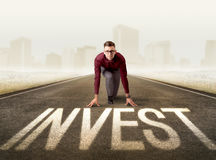 Businessman kneeling in ready position. Young determined businessman kneeling before invest sign Stock Photography