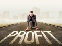 Businessman kneeling in ready position. Young determined businessman kneeling before profit sign Stock Photos