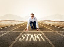 Businessman kneeling in ready position. Young determined businessman kneeling before start line Royalty Free Stock Photo
