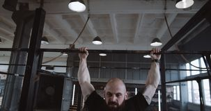 Young determined Caucasian athletic man doing pull-ups during functional workout training in large gym slow motion. Healthy lifestyle and bodybuilding, amateur stock footage