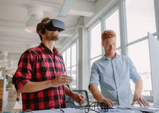 Young developers improving virtual reality glasses. Young developer working on laptop and virtual reality glasses. Two men improving virtual reality glasses in stock image