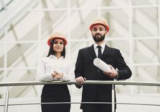 Young developers looking at camera. Creative team of two happy male and female colleagues in hardhats Stock Image