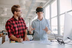 Young developers testing new virtual reality device. Shot of two young men testing virtual reality glasses in office. Businessman wearing VR goggles and royalty free stock images