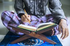Young devout man reading Quran. Closeup of young devout man reading Quran after doing Salat at home royalty free stock photo