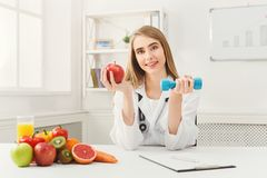 Young dietitian with apple and dumbbell at clinic. Smiling woman nutritionist holding fruit and sport equipment. Weight loss, healthy eating and slimming Royalty Free Stock Image