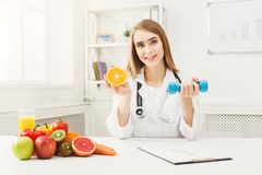 Young dietitian with orange and dumbbell at clinic stock images