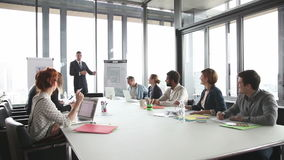Young director giving presentation to colleagues in conference room