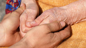 A young dirty working male hands comforting an elderly pair of hands of grandmother outdoor close up. Royalty Free Stock Photography