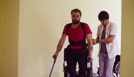 Young disable man in the robotic exoskeleton. Young disable men in the robotic exoskeleton sitting in wheelchair in the rehabilitation clinic royalty free stock photos