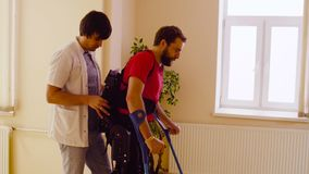 Young disable man in the robotic exoskeleton. Young disable men in the robotic exoskeleton sitting in wheelchair in the rehabilitation clinic stock image