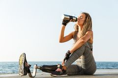 Young disabled athlete woman with prosthetic leg. Sitting at the beach and drinking water from a bottle stock image