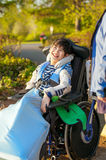 Young disabled boy in wheelchair enjoying park outdoors Royalty Free Stock Photography