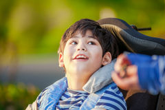 Young disabled boy in wheelchair looking up into sky. Handsome disabled nine year old boy sitting in wheelchair outdoors looking up into sky royalty free stock photography