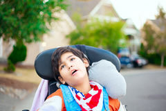 Young disabled boy in wheelchair looking up into sky Royalty Free Stock Photo