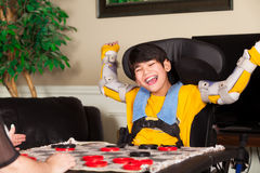 Young disabled boy in wheelchair playing checkers. Young biracial disabled boy in wheelchair playing checkers at home. Child has cerebral palsy Royalty Free Stock Images