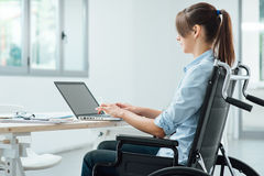 Young disabled businesswoman at work. Young disabled business woman in wheelchair working at office desk and typing on a laptop, accessibility and independence Stock Image