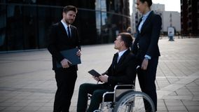Young disabled entrepreneur businessman talk with his coworkers and sign textpad docs stock video