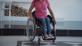 Woman in comfort wheelchair spending day at home. Young disabled female wearing in denim jeans clothes sitting in special invalid chair or handicap in house with stock video footage