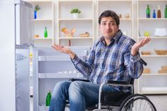 The young disabled injured man opening the fridge door Stock Images