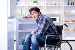 The young disabled injured man opening the fridge door Stock Image
