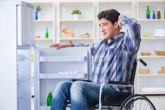 The young disabled injured man opening the fridge door Royalty Free Stock Images