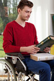 The young disabled looking of book Stock Photography