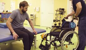 Free Young Disabled Man Going To Sit Down In A Wheelchair Royalty Free Stock Photos - 128869998