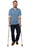 Young disabled man walking with forearm crutches. Young disabled man wearing casual clothes while walking with forearm crutches during recovery, full length, on Royalty Free Stock Photo