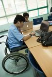 A young disabled student doing his homework on a computer, in a classroom stock photo