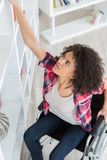 Young disabled woman reaching book on shelf. Female royalty free stock images