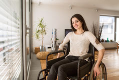 Young disabled woman in wheelchair at home in living room. Stock Images