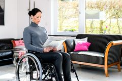 Disabled woman in wheelchair at home reading newspaper and drink stock image