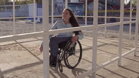 Young disabled woman in wheelchair resting on the beach in area for people with disabilities at evening autumn or spring. Time. 60 fps stock footage