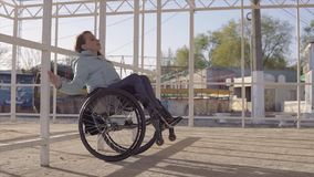 Young disabled woman in wheelchair resting on the beach in area for people with disabilities at evening autumn or spring. Time. 60 fps stock video footage