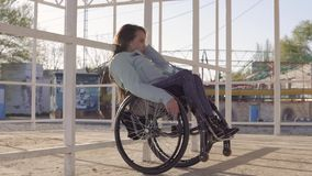 Young disabled woman in wheelchair resting on the beach in area for people with disabilities at evening autumn or spring. Time. 4k UHD stock video footage