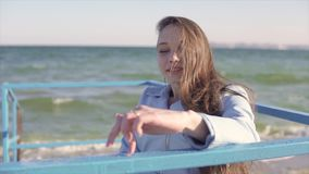 Young disabled woman in wheelchair shows fingers step walking by the handrails on the ramp for people with disabilities. Near the sea. 60 fps stock footage