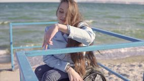 Young disabled woman in wheelchair shows fingers step walking by the handrails on the ramp for people with disabilities. Near the sea. 60 fps stock video footage