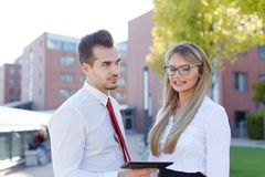 Young disappointed CEO with personal assistant. Outdoors royalty free stock photography