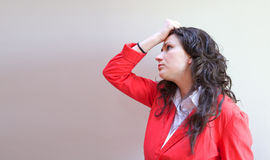 A young disappointed lady. A young lady between 20 and 30 years old dressed in a coral jacket and white blouse demonstrates her disappointment stock images