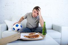 Young disappointed man watching football game on television sad  desperate and frustrated Stock Photos