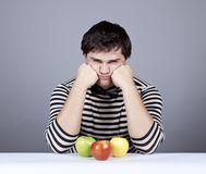 The young disappointed men with three apples Royalty Free Stock Photos