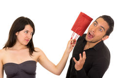 Young disappointed woman hits man with gift bag Stock Photo