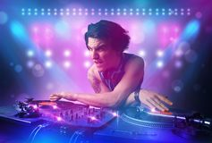 Disc jockey mixing music on turntables on stage with lights and stroboscopes. Young disc jockey mixing music on turntables on stage with lights and stroboscopes Royalty Free Stock Photos